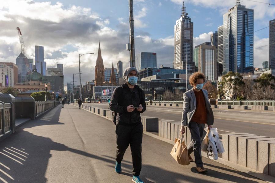 Pedestrians walk with masks on in Melbourne, Australia.