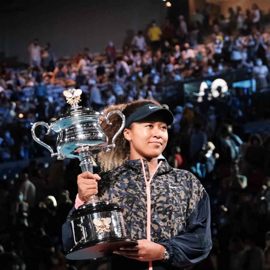 Naomi Osaka holding her 2021 Australian Open championship trophy.